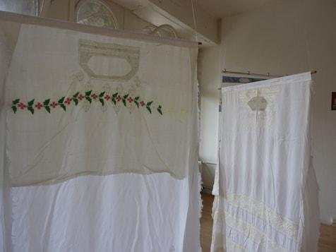 Blick in die Ausstellung in Leipzig, bestickten Vorderteile von  Tshaderis als Mobile montiert, Juni 2012